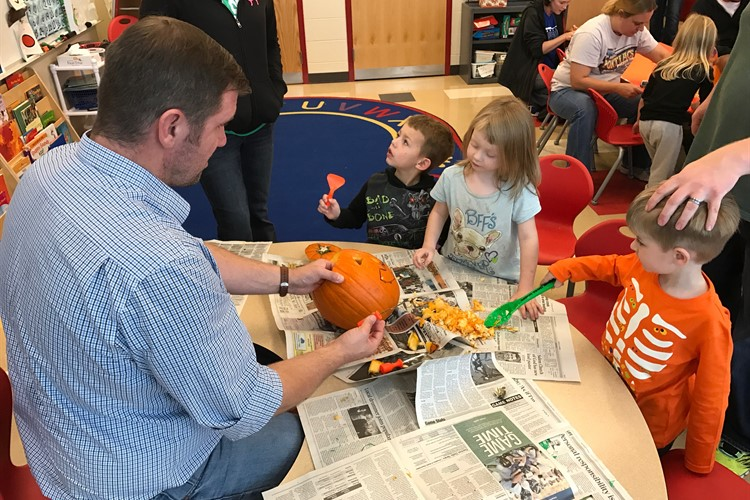 Mr. Allen assists his students at BES as they carve pumpkins during their harvest party.