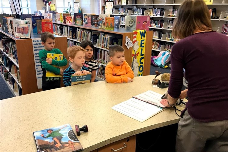 Elementary Students Check-out Books in the Library
